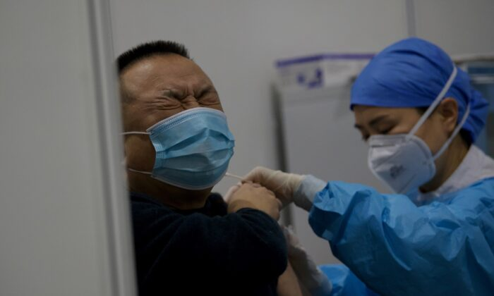 A medical worker inoculates a man with a COVID-19 vaccine at the Chaoyang Museum of Urban Planning in Beijing, on Jan. 15, 2021. (Noel Celis/AFP via Getty Images)