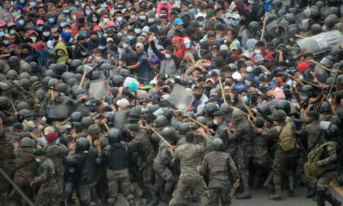 Honduran migrants, part of a caravan heading to the United States, clash with Guatemalan security forces in Vado Hondo, Guatemala, on Jan. 17, 2021. (Johan Ordonez/AFP via Getty Images)