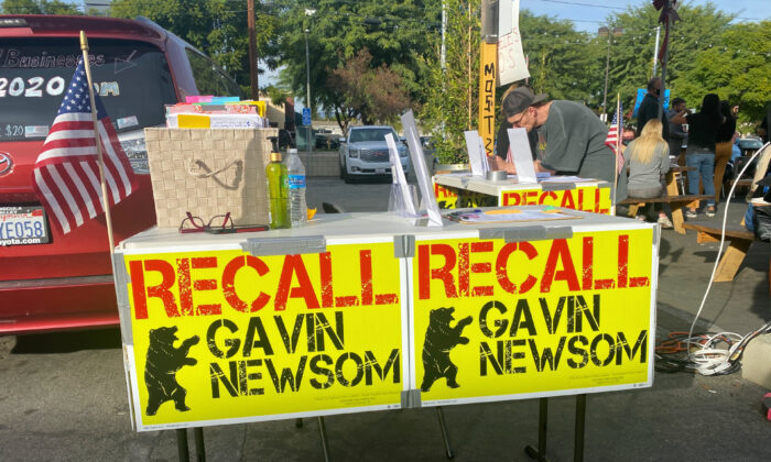 A man looks at items on a table calling for the recall of Gov. Gavin Newsom outside the Pineapple Hill Saloon & Grill in Sherman Oaks, Calif., on Jan. 7, 2021. (Jamie Joseph/The Epoch Times)