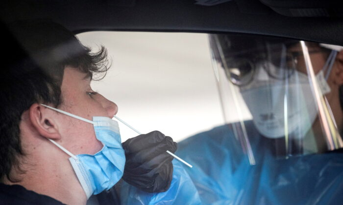 A health care worker gives a CCP virus test at a COVID-19 drive-thru testing center at Bergen Community College in Paramus, N.J., on Dec. 3, 2020. (Brendan McDermid/Reuters)
