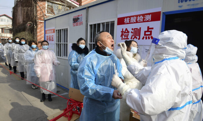 "Residents undergo Covid-19 coronavirus tests at a makeshift testing centre inside a residential compound in Shijiazhuang, in northern Hebei province on Jan. 16, 2021, as part of a mass testing program after the province declared an ""emergency state.""(STR/CNS/AFP via Getty Images)"