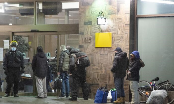 People lineup at a hotel for the homeless before the 8 p.m. COVID-19 curfew on Jan. 11, 2021, in Montreal. (Ryan Remiorz/The Canadian Press)