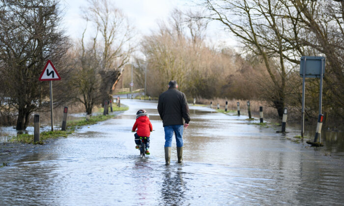 A child cycles along the flooded road by the side of the River Great Ouse in Cambridgeshire, England, after it was closed due to flood waters on Jan. 19, 2021. (Leon Neal/Getty Images)