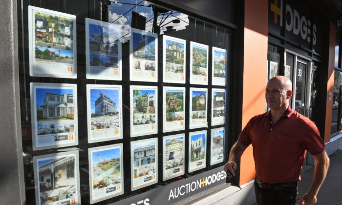 A man walks past a real estate agent's window advertisements in Melbourne on May 1, 2019. (Photo by WILLIAM WEST/AFP via Getty Images)