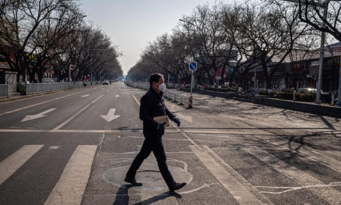 A man wearing a protective mask and gloves walks on a nearly empty street in Beijing on Feb. 23, 2020. (Nicolas Asfouri/AFP via Getty Images)