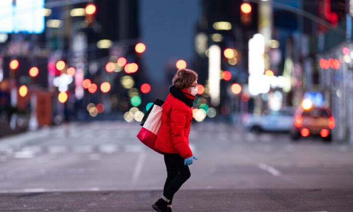 A woman walks through an almost-deserted Times Square in the early morning hours in New York City on April 23, 2020. (Johannes Eisele/AFP via Getty Images)