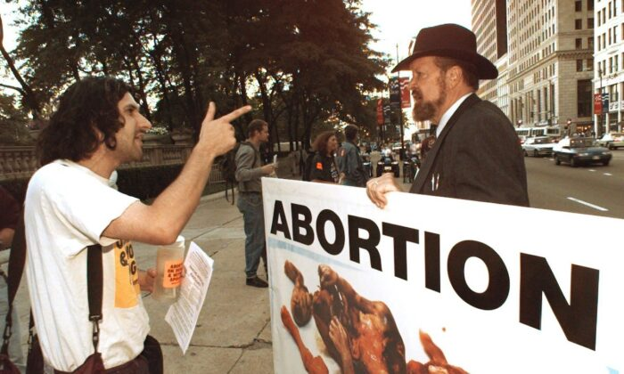 Joe Scheidler, the founder of the Pro-Life Action League, carries a sign along Michigan Ave. in Chicago, on Aug. 23, 1996. (AP Photo/John Gaps III, file)