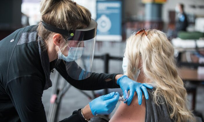 A woman receives a CCP virus vaccine at Gillette Stadium in Foxborough, Mass., on Jan. 15, 2021. (Scott Eisen/Getty Images)