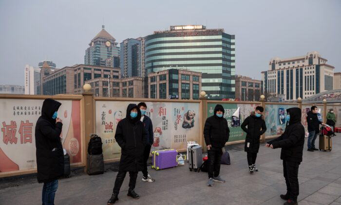 People wearing masks wait next to their suitcases at the Beijing railway station in Beijing on Jan. 27, 2020. (Nicolas Asfouri/AFP via Getty Images)