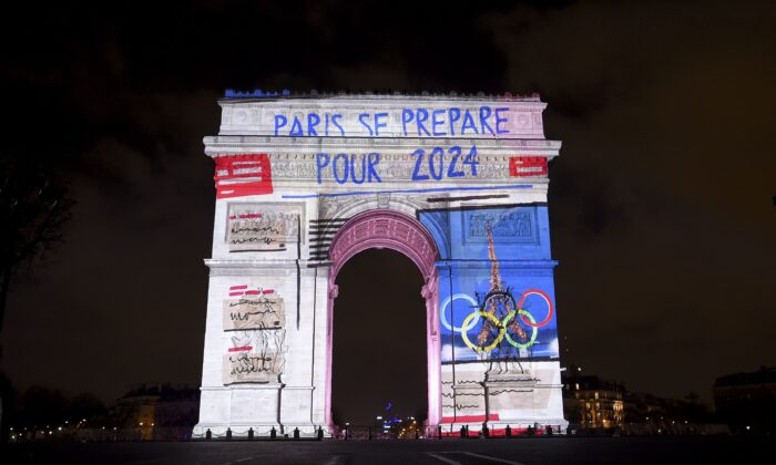 """Images with a slogan reading """"Paris is getting ready for 2024,"""" referring to the 2024 Olympic Games that Paris was awarded, are projected on the Arc de Triomphe monument during a laser and 3D video mapping show as part of the New Year celebrations in Paris on Dec. 31, 2017. (Guillaume Souvant/AFP via Getty Images)"""