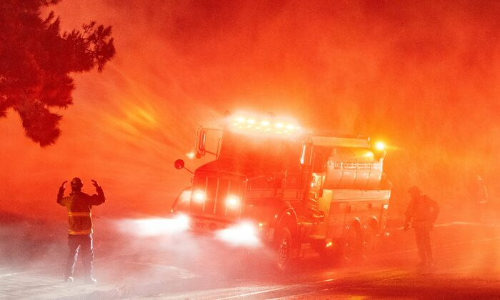 Firefighters spray down flames on the side of Interstate 210 in Sylmar, Calif., on Jan. 19, 2021. (Josh Edelson/AFP via Getty Images)