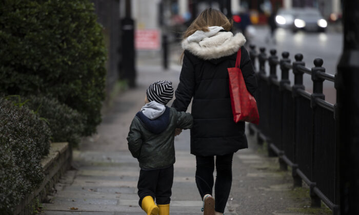 A child and parent walk near a closed primary school in Deptford, London, on Jan. 4, 2021. (Dan Kitwood/Getty Images)