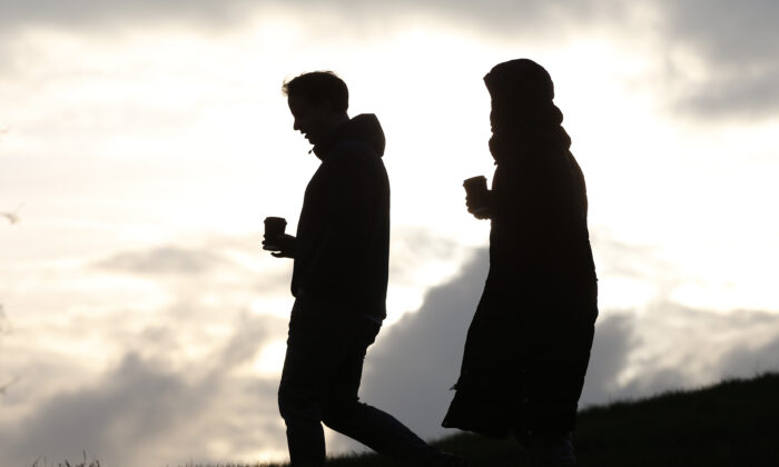 People walk with drinks as they do their daily exercise at Primrose Hill in London on Jan. 15, 2021. (Hollie Adams/Getty Images)