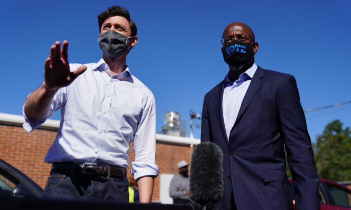 Democratic U.S. Senate candidates Jon Ossoff and Rev. Raphael Warnock hand out lawn signs at a campaign event in Lithonia, Ga., on Oct. 3, 2020. (Elijah Nouvelage/Getty Images)