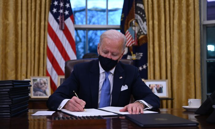 President Joe Biden sits in the Oval Office as he signs a series of orders at the White House after being sworn in at the US Capitol on Jan. 20, 2021. (JIM WATSON/AFP via Getty Images)