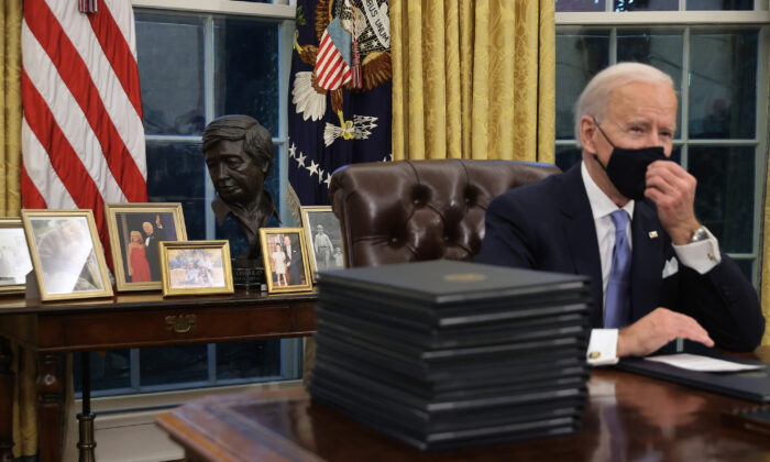 President Joe Biden prepares to sign a series of executive orders at the Resolute Desk in the Oval Office in Washington, on Jan. 20, 2021. (Chip Somodevilla/Getty Images)