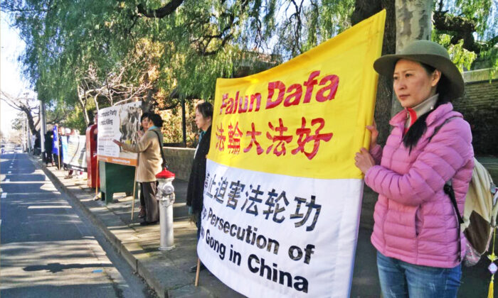 "Angel holding the banner of ""Stop Persecuting Falun Gong"" opposite the main entrance of the Chinese Consulate in Toorak in Melbourne, Australia. (Courtesy of Angel)"