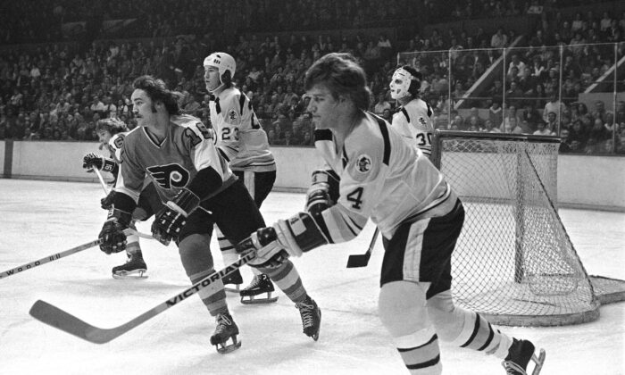 The renowned Bobby Orr of the Boston Bruins (R) passes the puck during a game at the Boston Garden on Feb. 9, 1974. Next to him is the Philadelphia Flyers' Rick MacLeish. (The Canadian Press/AP)