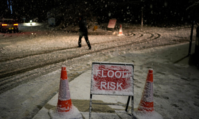 Danger to life flood warnings are given along the River Mersey in East Didsbury, West Didsbury and Northenden as Storm Christoph moves in on the UK. A person walks past a snow-covered flood warning sign in Didsbury, United Kingdom, on Jan. 20, 2021. (Christopher Furlong/Getty Images)