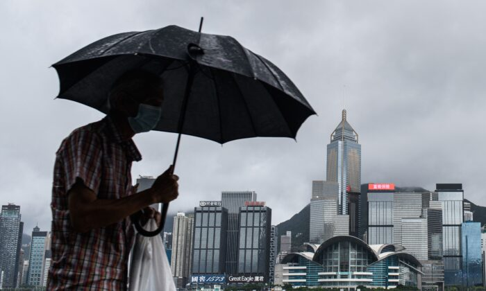 A man uses his umbrella on Kowloon's Tsim Sha Tsui waterfront that faces Victoria Harbor and the Hong Kong Island skyline (back) in Hong Kong on Aug. 19, 2020. (Anthony Wallace/AFP via Getty Images)