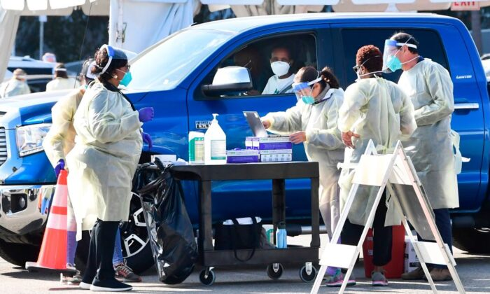 People pull up in their vehicles for COVID-19 vaccines in the parking lot of The Forum in Inglewood, California on January 19, 2021.  (Frederic J. Brown BROWN/AFP via Getty Images)