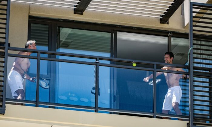 Support Staff (L) and Serbian World No.1 Tennis player Novak Djokovic (R) quarantined at the M Suites in North Adelaide in Adelaide, South Australia, January 20, 2021, ahead of the Australian Open Tennis Tournament. (Morgan Sette/AFP via Getty Images)