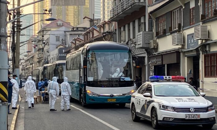 Police and workers arrange buses to remove all residents at a neighborhood in Huangpu district to quarantine centers, in Shanghai on Jan. 21, 2021. (AFP via Getty Images)