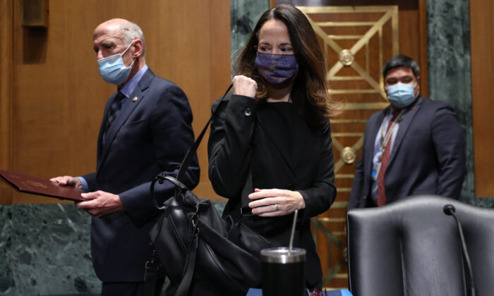 Avril Haines (C) and Dan Coats (L), former Director of National Intelligence, arrive at the start of the Senate Intelligence Committee confirmation hearing in Washington to consider her to be President Joe Biden's pick for national intelligence director on Jan. 19, 2021. (Joe Raedle/Getty Images)