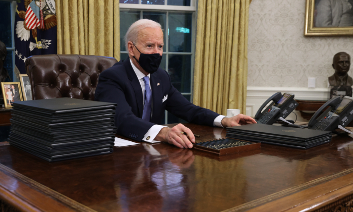 President Joe Biden prepares to sign a series of executive orders at the Resolute Desk in the Oval Office in Washington just hours after his inauguration on Jan. 20, 2021. (Chip Somodevilla/Getty Images)