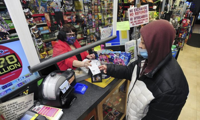 Jacqueline Donahue of Hazleton, right, buys a Mega Millions lottery ticket at the Anthracite Newsstand on Public Square on Jan. 18, 2021, in Wilkes-Barre, Pa. (Mark Moran/The Citizens' Voice via AP)
