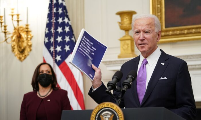 President Joe Biden speaks about the COVID-19 response as Vice President Kamala Harris looks on, before signing executive orders in the State Dining Room of the White House in Washington on Jan. 21, 2021. (Mandel Ngan/AFP via Getty Images)