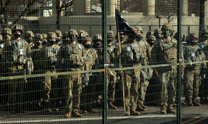 National Guard troops stand at attention outside security fencing along Pennsylvania Avenue as President-elect Joe Biden's motorcade drives past on its way to the U.S. Capitol in Washington on Jan. 20, 2021. (Chip Somodevilla/Getty Images)