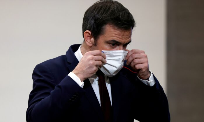 French Health Minister Olivier Veran puts on his face mask after a press conference in Paris, France on Jan. 14, 2021. (Thomas Coex/Pool via Reuters)