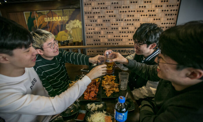 Young South Koreans drink beer and eat deep-fried chicken dishes at a restaurant in Seoul, South Korea on March 10, 2017. (Jean Chung/Getty Images)