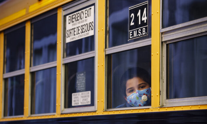 A student peers through the window of a school bus as he arrives at the Bancroft Elementary School in Montreal, Canada, on Aug. 31, 2020. (Paul Chiasson/The Canadian Press)