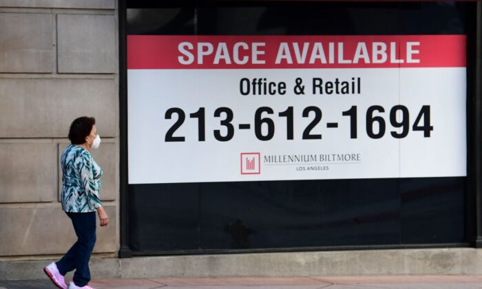 A woman walks past advertising for office and retail space available in downtown Los Angeles on May 4, 2020. (Fredric J. Brown/AFP via Getty Images)
