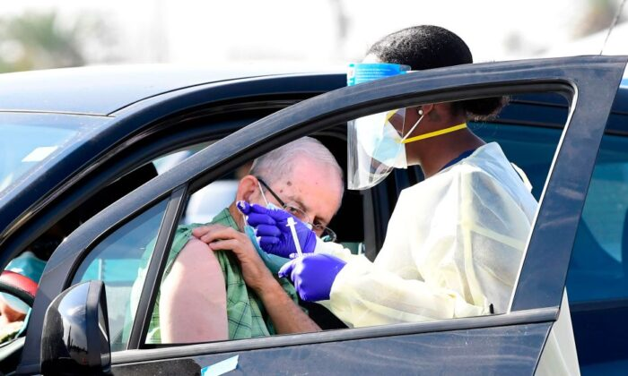 People pull up in their vehicles for COVID-19 vaccines in the parking lot of The Forum in Inglewood, Calif., on Jan. 19, 2021.  (Frederic J. BROWN/AFP via Getty Images)