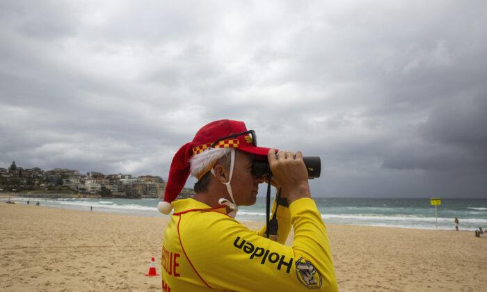 A surf rescue worker wearing a Santa hat looks through binoculars at Bondi Beach in Sydney, Australia on Dec. 25, 2020. (Jenny Evans/Getty Images)