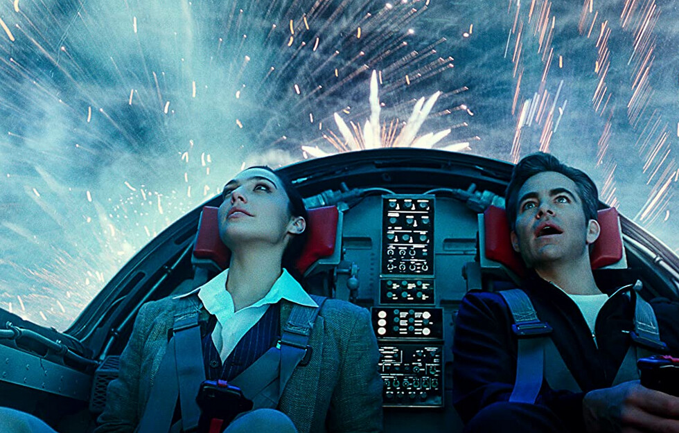 """man and woman in jet cockpit look at fireworks in """"Wonder Woman 1984"""""""