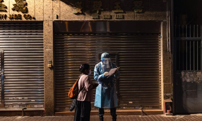 A health worker speaks to a resident at a temporary testing site where COVID-19 cases have been confirmed in the Jordan district in Hong Kong on Jan. 20, 2021. (Anthony Kwan/Getty Images)