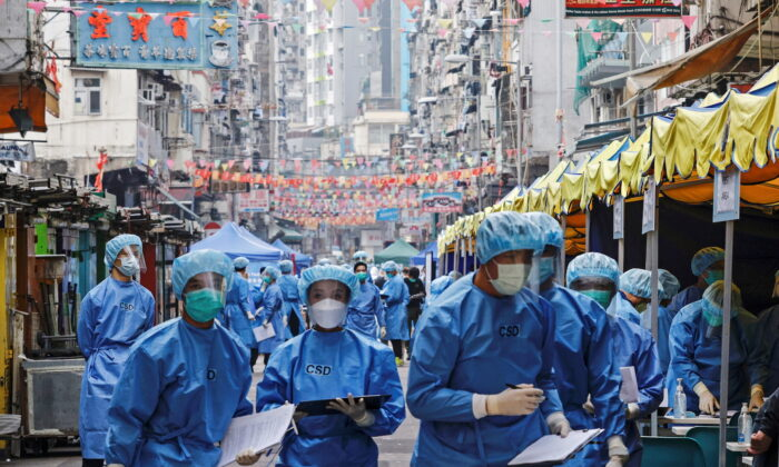 Health workers are seen in protective gear inside a locked down portion of the Jordan residential area to contain a new outbreak of COVID-19 in Hong Kong on Jan. 23, 2021. (Tyrone Siu/Reuters)