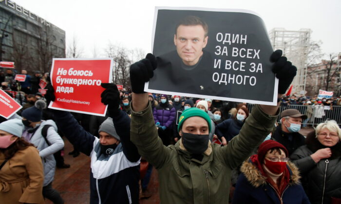 """A participant holds a placard reading """"One for all, all for one"""" during a rally in support of jailed Russian opposition leader Alexei Navalny in Moscow, Russia on Jan. 23, 2021. (Maxim Shemetov/ REUTERS)"""