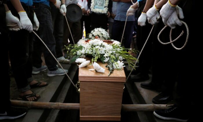 Locals and relatives of Anna Bui Thi Nhung, one of the 39 Vietnamese people found dead in a truck near London in October, prepare bury her coffin during her funeral at a cemetery in Nghe An province, Vietnam, on Dec. 1, 2019. (Kham/Files, Reuters)