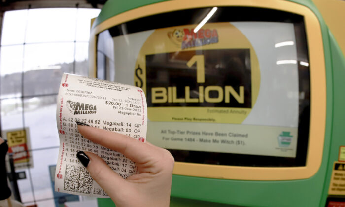 A patron, who did not want to give her name, shows the ticket she had just bought for the Mega Millions lottery drawing at the lottery ticket vending kiosk in a store in Cranberry Township, Pa., Jan. 22, 2021. (Keith Srakocic/AP Photo)