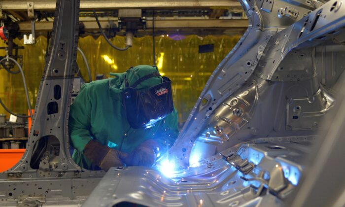 Line workers spot weld parts of the frame on the flex line at Nissan Motor Co's automobile manufacturing plant in Smyrna, Tenn., on Aug. 23, 2018. (William DeShazer/Reuters)
