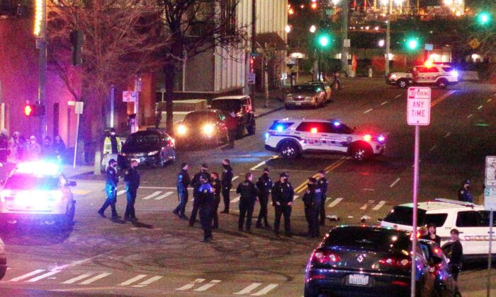 Tacoma Police and other law enforcement officers stand in an intersection near the site of a car crash in downtown Tacoma, Wash., on Jan. 23, 2021. (Ted S. Warren/AP Photo)