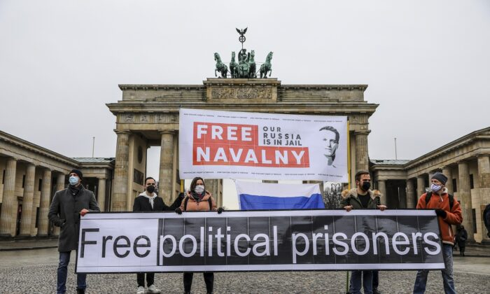 """Protesters hold banners reading """"FREE NAVALNY"""" and """"FREE POLITICAL PRISONERS"""" in front of the Brandenburg Gate in Berlin, on Jan. 23, 2021. (Omer Messinger/Getty Images)"""