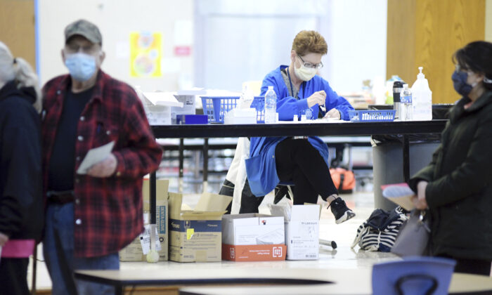 Visitors to an Ashtabula County Health Department COVID-19 vaccination clinic wait for service as vaccines are prepared, back center, at Jefferson Elementary School in Jefferson, Ohio on Jan. 23, 2021. (Ashtabula Star Beacon, Warren Dillaway/AP)