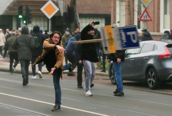A demonstrator throws a sign
