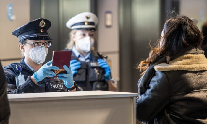 Officers of the German Federal Police check passengers arriving by plane from Prague at the Frankfurt Airport in Frankfurt, Germany, on Jan. 24, 2021. (Boris Roessler/dpa via AP)